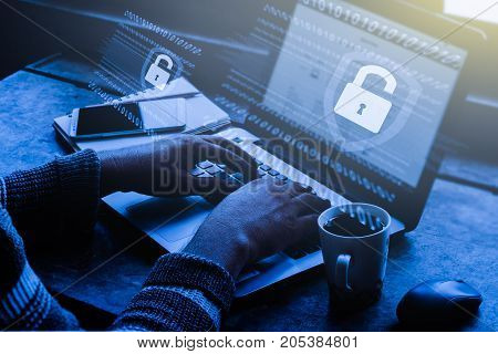 Business, technology, internet and networking concept. Young businessman working on his laptop in the office, select the icon security on the virtual display / Blue tone