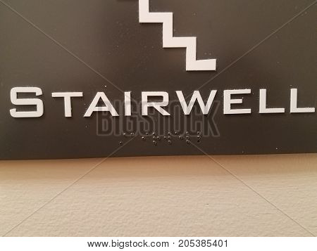 braill dots on a dark colored plastic sign