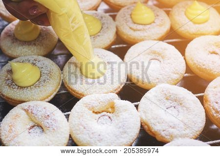 vanilla flavoured filling into a sweet doughnuts - Making bakery