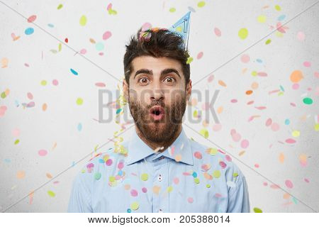 People, Joy, Birthday, Anniversary, Fun And Party Concept. Picture Of Handsome Astonished Young Man