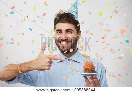 Picture Of Euphoric Young Man In Formal Wear Celebrating Anniversary, Holding Cupcake And Pointing I