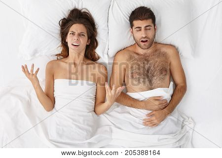 Furious Female Gestures In Bed With Anger, Being Fed Up With Husband`s Snoring, Has Sleepless Night.