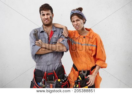 Portrait Of Two Plumbers Man And Female Wearing Work Clothes And Waist Bags With Working Instruments