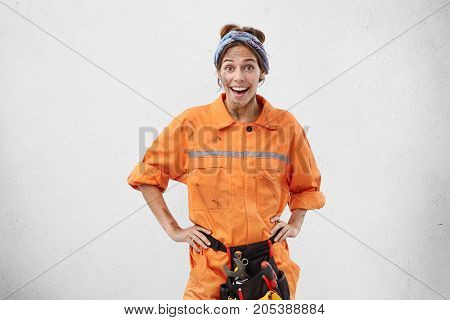 Waist Up Portrait Of Happy Female Carpenter, Wears Orange Unifrom With Tool Belt, Recieves Pleasant