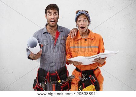 Waist Up Portrait Of Astonished Puzzled Home Repairman And Female Maintenance Worker Hold Blueprint