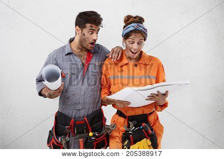 Isolated Studio Portrait Of Astonished Emotional Young Caucasian Man And Woman Engineers Holding Blu