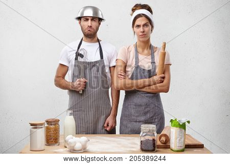 Indoor Shot Of Discouraged Male And Female Restaurant Workers, Stand Near Table With Kitchen Supplie