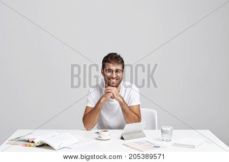 Horizontal Portrait Of Stylish Young Freelancer Works At Office, Has Positive Expression, Uses Moder