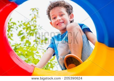 kid boy having fun to play on children's climbing toy at school playgroundback to school activity