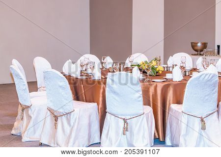An event dinner set up with white seat covers and bronze table cloth.