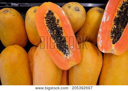Slice of sweet papaya on papaya pile.