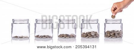 Hand Holding Thai Coin (baht) And Insert To Clear Glass Jar. Studio Shot Isolated On White. Save Mon