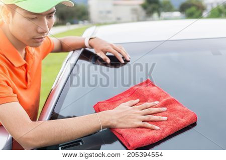 Young Man Using Red Microfiber Cloth Cleaning Body Of New Silver Car. For Car Maintenance Concept..