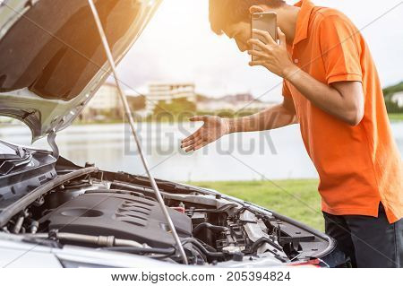 Asian Man Calling And Checking His Damaged Car. For Car Repair Concept