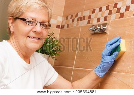 Elderly Senior Woman With Sponge Cleaning And Washing Bathroom Tiles, Household Duties Concept