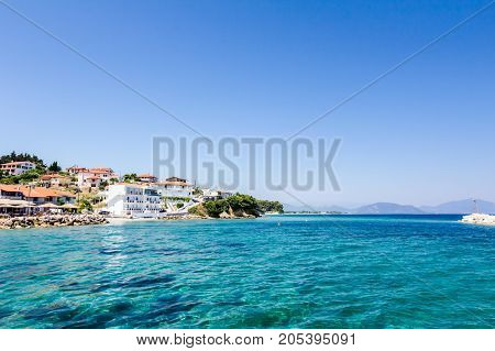 Low angle view on the stony beach with beautiful shallow turquoise water and town over sea.