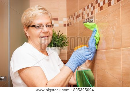 Senior Woman Washing Tiles Using Microfiber Cloth With Detergent, House Cleaning And Household Dutie