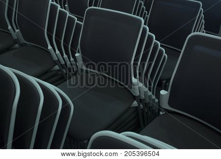 Multiple stacked chairs. Dark color furniture plastic.