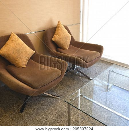 Two brown armchair and yellow cushions in living room.