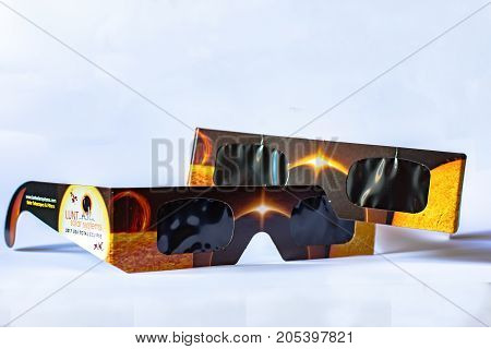 Illustrative editorial image of two pairs of solar Lunt Solar Systems eclipse viewing glasses on a white background