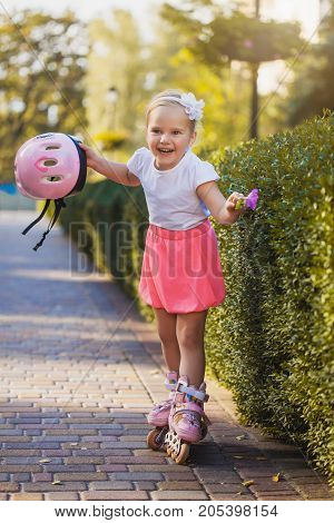 smiling Little girl on roller skates at summer park