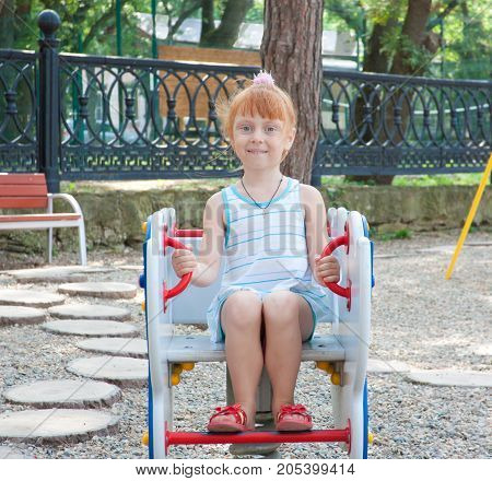 Little red-haired girl at the various attractions