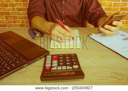 Close up of businessman hand holding pen working on calculator accountancy document and laptop computer at office e business concept. Businessperson working in office - Retro color