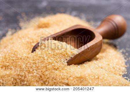 Brown Cane Sugar In A Wooden Scoop