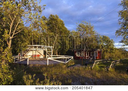 Outdoor, old wooden dance floor in the countryside. Seats and some red cabin, for sales.