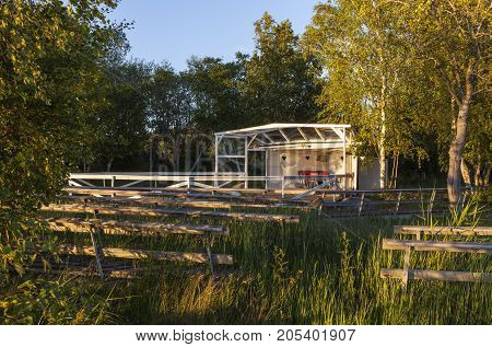 Outdoor, old wooden dance floor in the countryside. Seats and some red cabin, shelter.