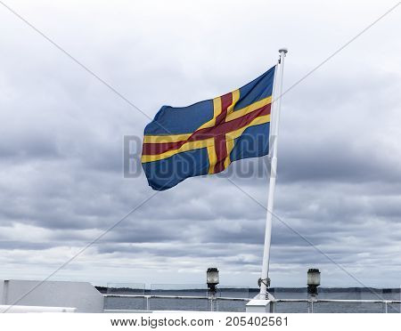 Aland, National flag, standard at the stern on a ship waving in the wind. The Baltic Sea in the background.