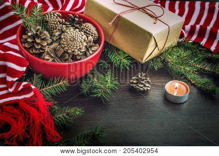 Christmas decoration - red bowl full of fir-cones gift box wrapped in kraft paper pine branches candle and red and white striped winter scarf. Christmas theme. Dark wooden background.