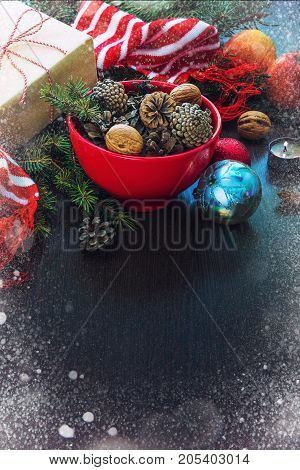 Christmas decoration - red bowl full of fir-cones gift box wrapped in kraft paper pine branches candle nuts anise apples christmas toys and red and white striped winter scarf. Christmas theme. Dark wooden background.Copy space. Snow frame.