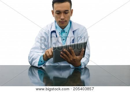 Asian young doctor using digital tablet computer for looking at patient information at clinic isolated on white background concept of medical technology innovation.