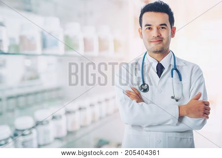 Asian smart doctor standing arms crossed and carrying stethoscope on shoulders at hospital with blurred drugstore background concept of business medical and pharmacist professional.