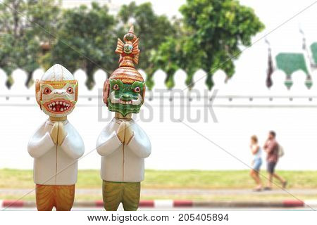 Doll Hanuman and Thotsakan respect hands sawasdee and uniform thai style with image blur wall of temple thailand.