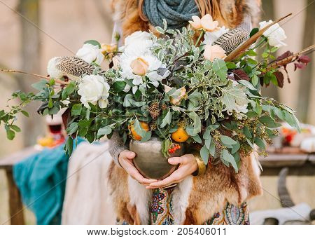arranging, fall, style concept. girl wearing ornamental dress and fox jacket holding vase with wondreful autumnal bunch composed of various flowers and decorated with leaves of eucaliptus and rosebush