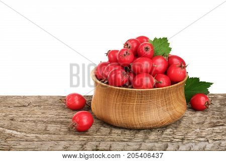 Hawthorn berry with leaf in a bowl on wooden table with white background.