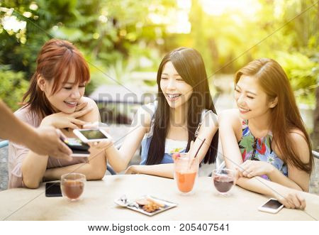 young woman paying bill with smart phone in restaurant