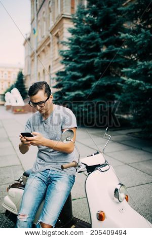 Handsome Happy Man Sitting On The Scooter Typing A Message On The Phone