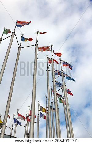 Flags Of Different Countries On Cloudy Sky Background