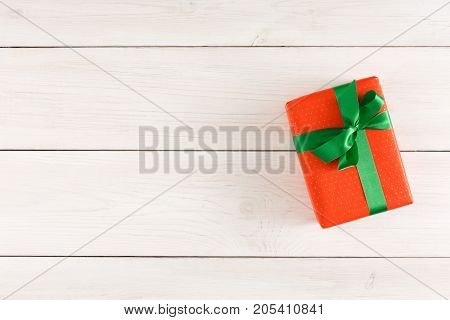 Top view on gift box in red wrapping paper tied with green satin ribbon on white rustic table with copy space. Christmas, birthday or valentine day present concept
