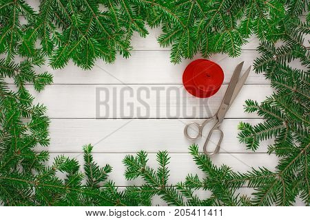 Christmas DIY background. Scissors and string jute on rustic wood with fir tree branches frame. Handmade hobby and winter holidays concept, top view, copy space.