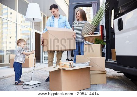Portrait of happy young family holding cardboard boxes standing next to moving van and smiling looking at their son