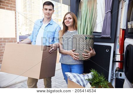 Portrait of happy young couple moving in new home, holding house plant and smiling looking at camera outdoors