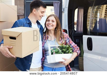 Portrait of happy  young couple embracing and smiling at camera holding cardboard boxes next to moving van outdoors