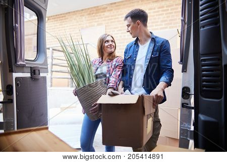 Portrait of happy young couple moving in new home, holding house plant and smiling looking at each other with love outdoors