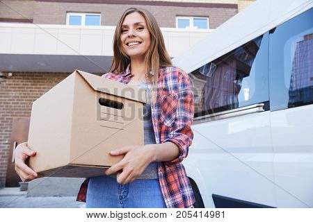 Portrait of happy young woman holding cardboard box and smiling to camera posing next to moving van