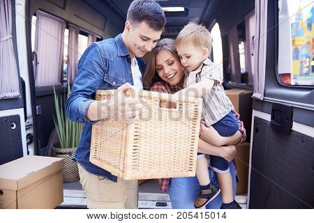 Portrait of happy young family with little boy unloading moving van outdoors and unpacking boxes smiling brightly