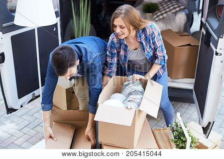 Young couple, man and woman, unloading moving van together opening cardboard boxes outdoors and smiling happily